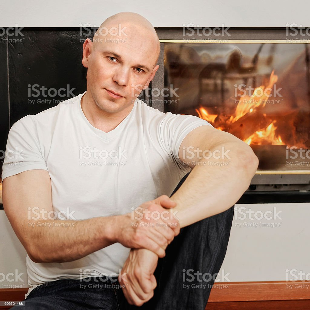 Handsome bald headed man sitting on fur carpet at fireplace stock photo