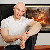Handsome bald headed man sitting on fur carpet at fireplace