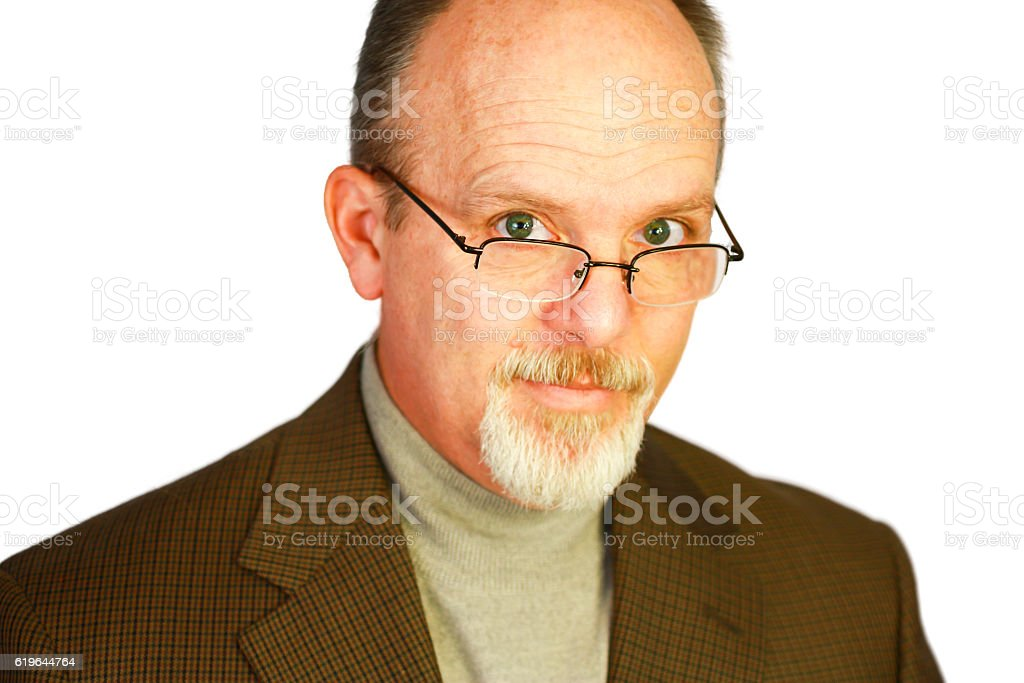 Handsome bald man with goatee looking over glasses stock photo