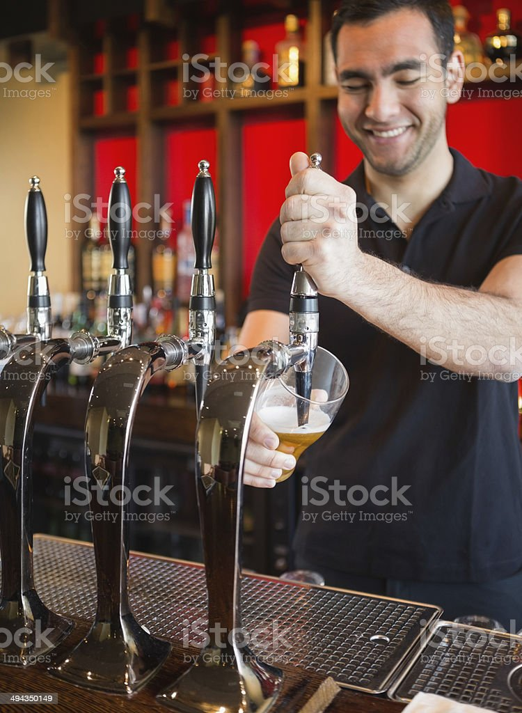 Handsome barkeeper pulling a pint of beer stock photo