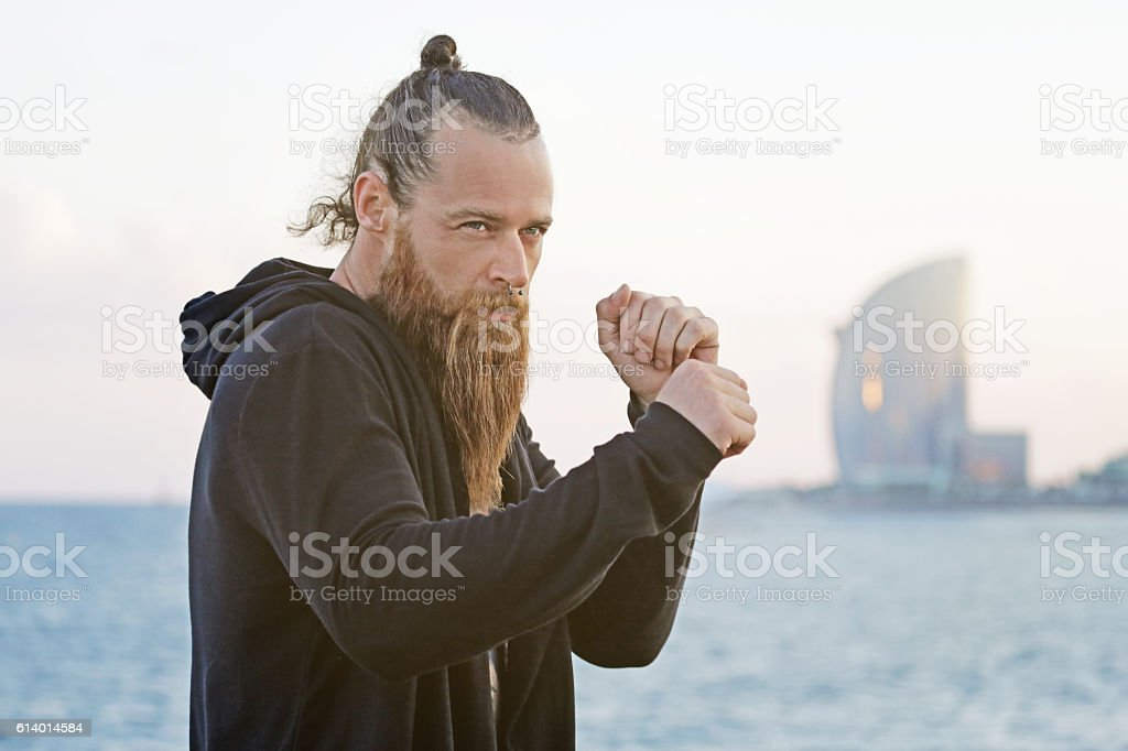 Handsome bearded boxer shadow boxing by the sea stock photo