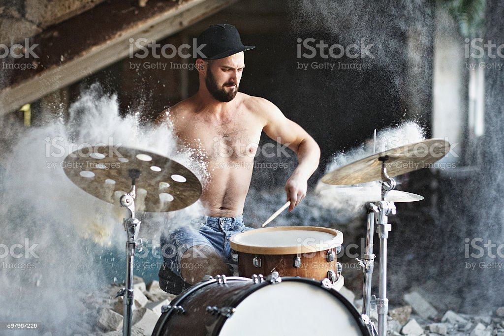 Handsome bearded guy plays drums stock photo