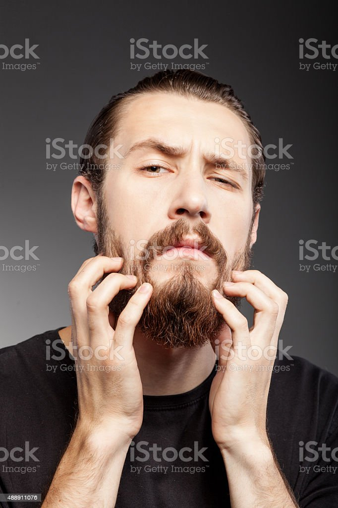 Handsome bearded hipster guy is caring of his appearance stock photo