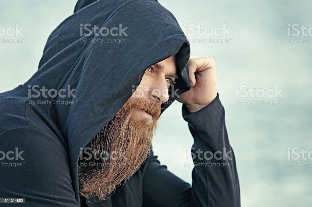 Handsome bearded hooded man sitting alone by the sea stock photo