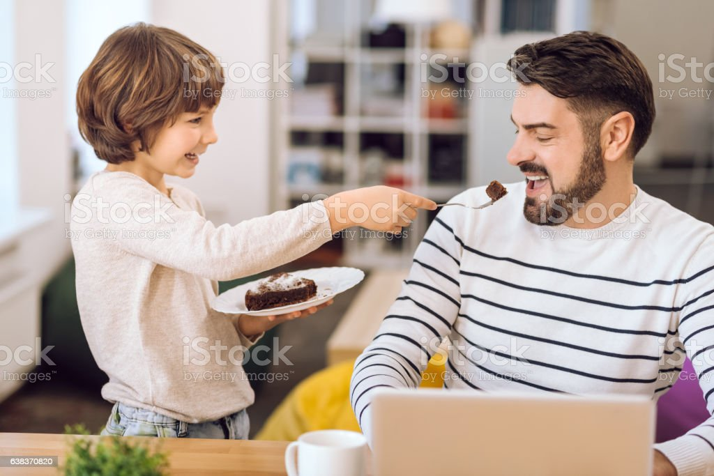 Handsome bearded man opening mouth for cake stock photo