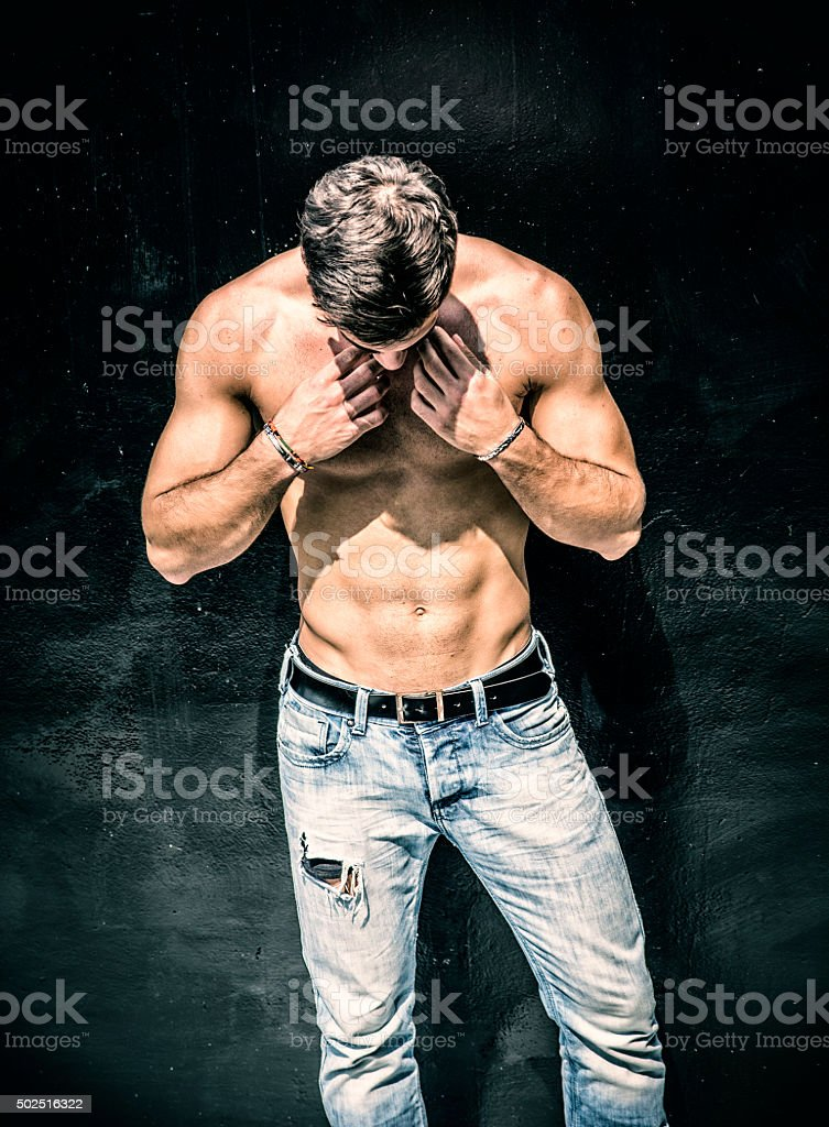 Handsome bearded shirtless young man standing against black wall stock photo