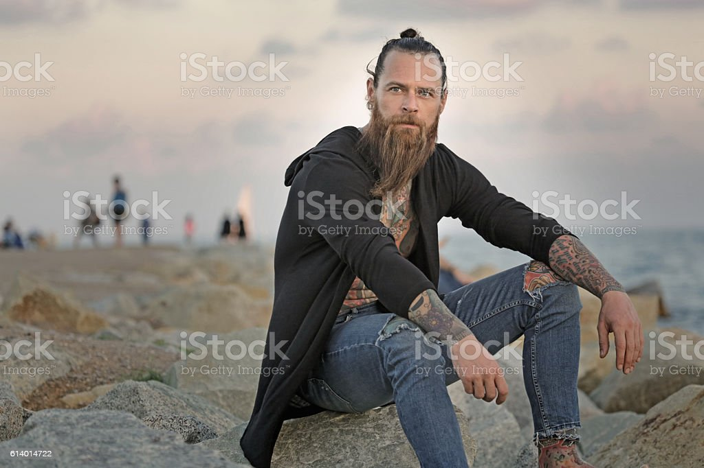 Handsome bearded tattooed man sitting alone by the sea stock photo