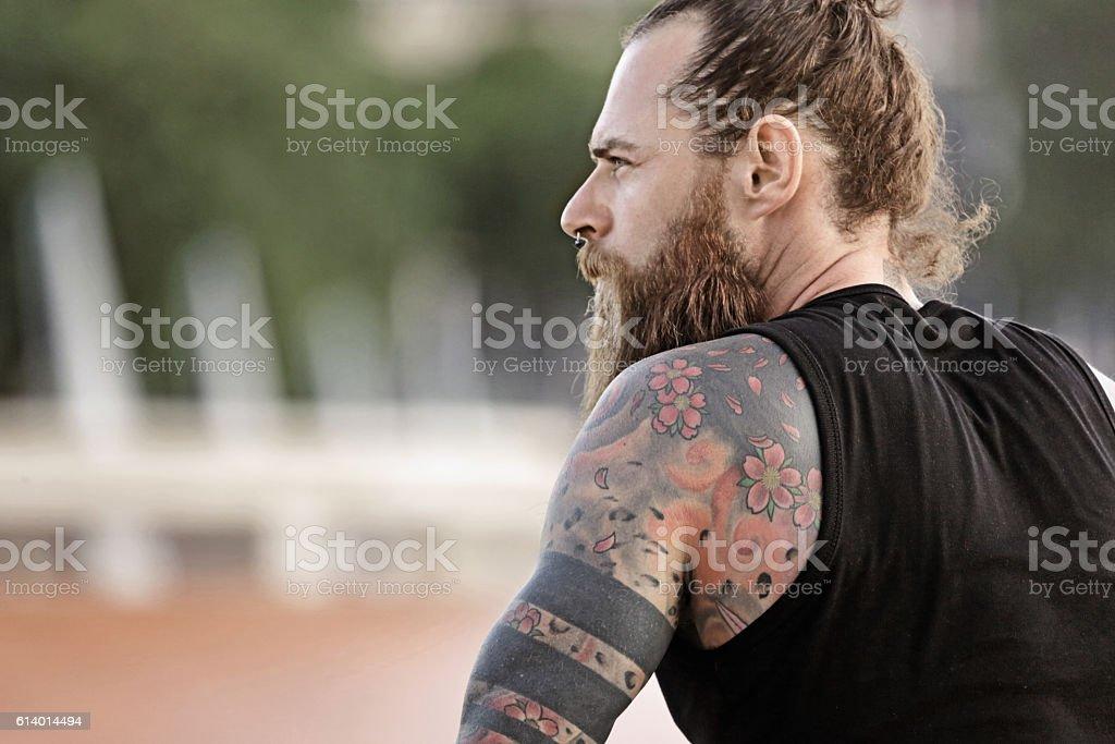 Handsome bearded tattooed man sitting alone in urban setting stock photo