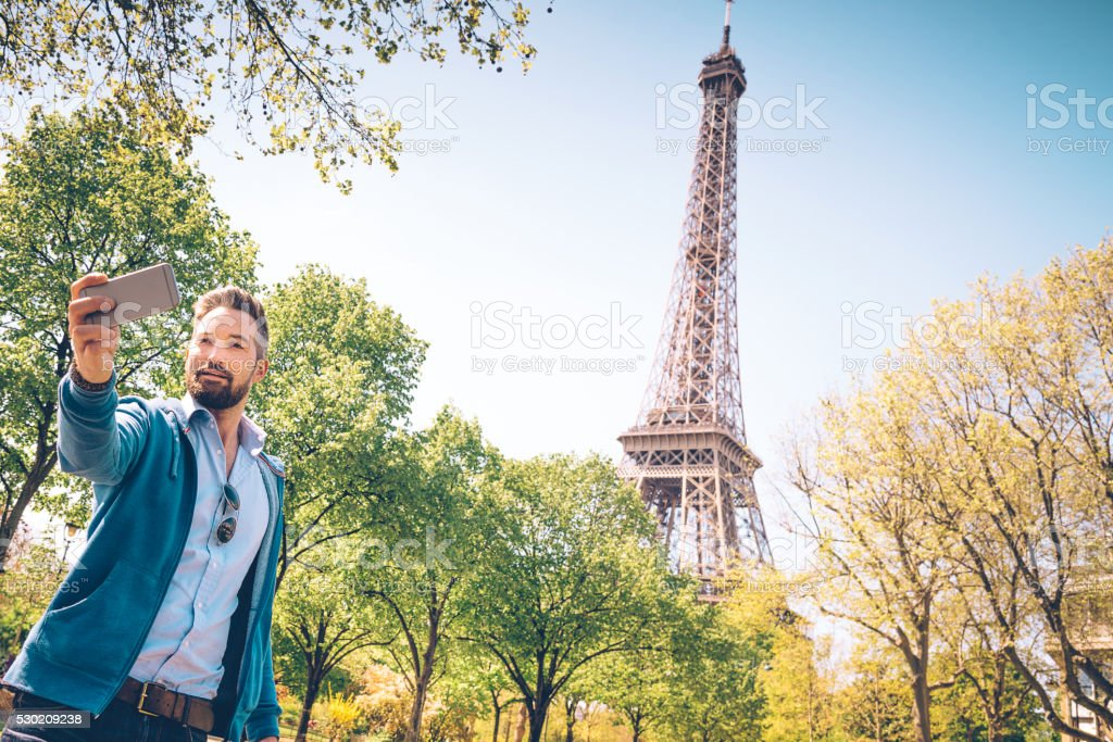 handsome bearded tourist taking selfie in park of Eiffel tower stock photo