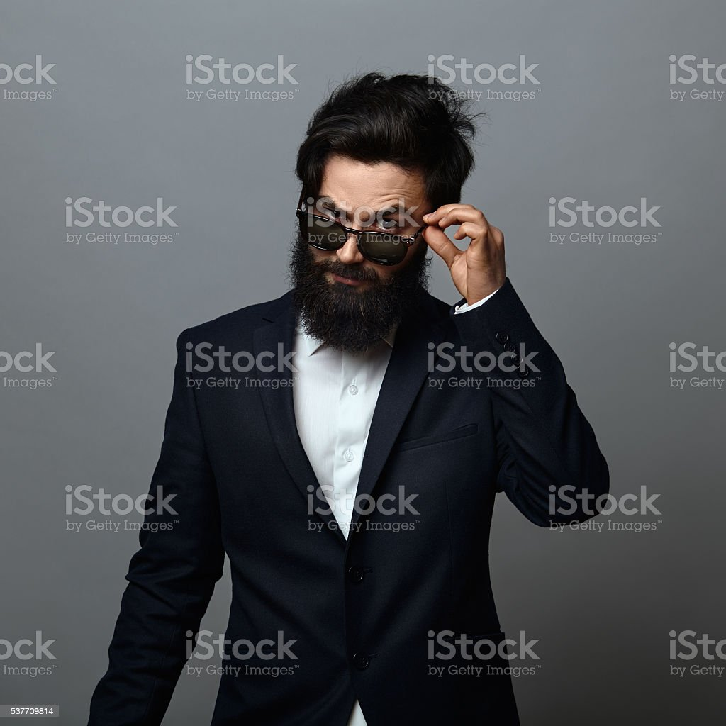 handsome bearded young man adjusting his sunglasses stock photo