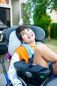Handsome biracial disabled boy in wheelchair, smiling outdoor, relaxing