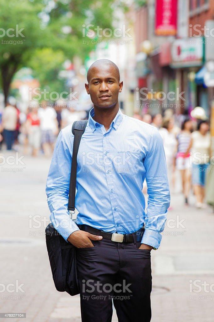 Handsome Black bald office worker street portrait with laptop bag stock photo