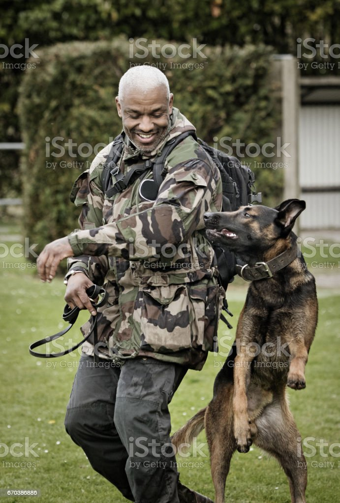 Handsome black middle aged man exercising with work dog at dog school
