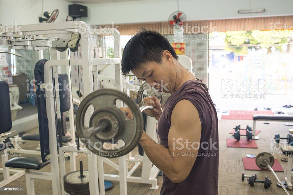 Handsome Bodybuilder performing barbell biceps curls stock photo