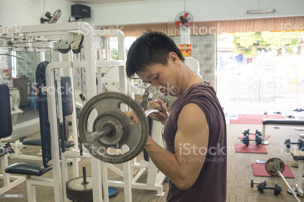 Handsome Bodybuilder performing barbell biceps curls stock photo