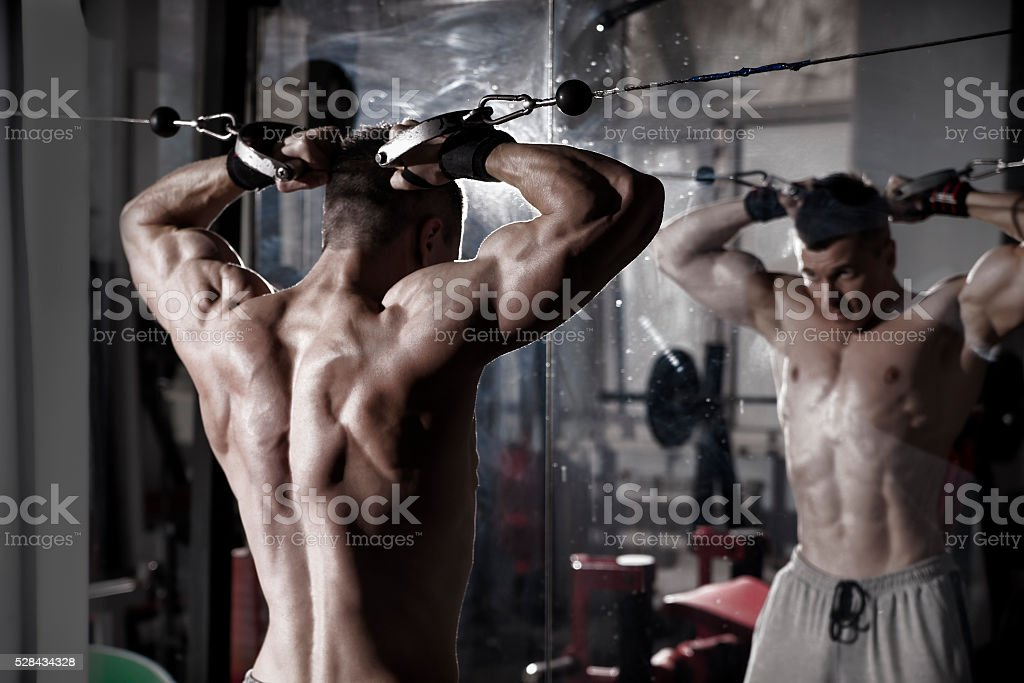 Handsome bodybuilder works out pushing up excercise in gym stock photo