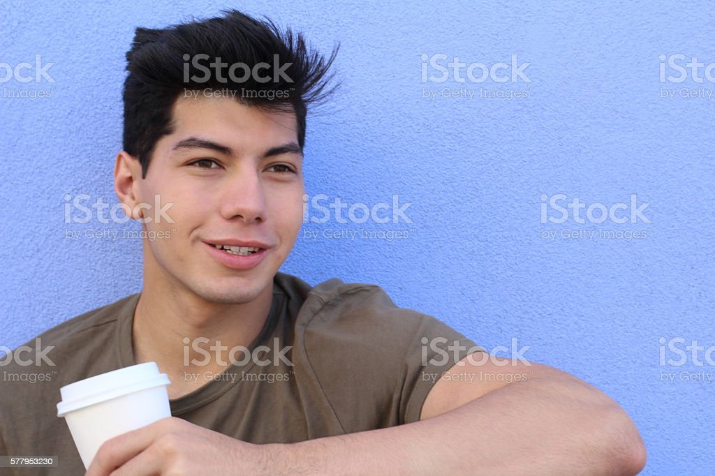 Handsome boy sitting in street with morning coffee stock photo