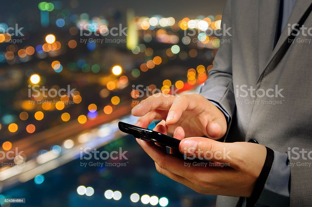 Handsome Business male in the city using his smartphone. stock photo
