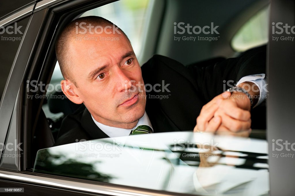 Handsome business man checking time in backseat of car royalty-free stock photo