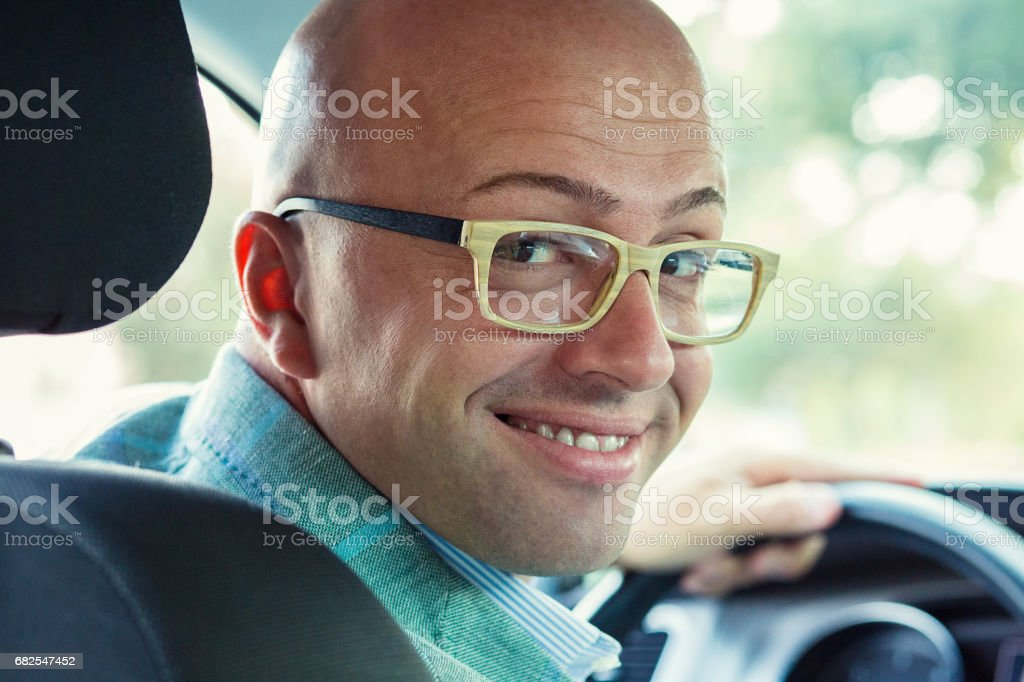 Handsome business man driver is sitting in his car stopped driving...
