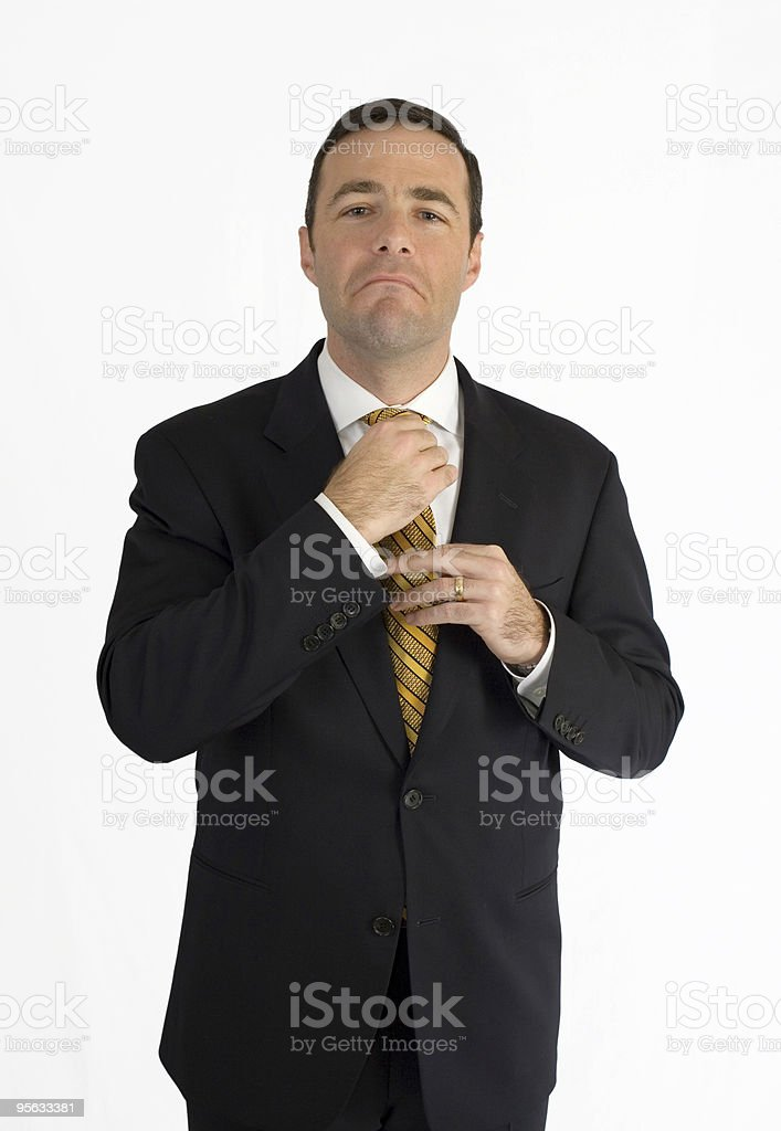 Handsome business man in black suit adjusting tie stock photo