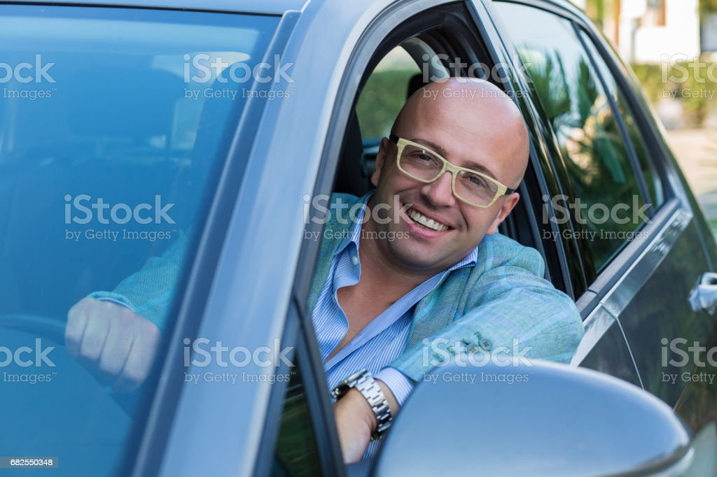 Handsome business man smiling looking out of his new car window stock photo