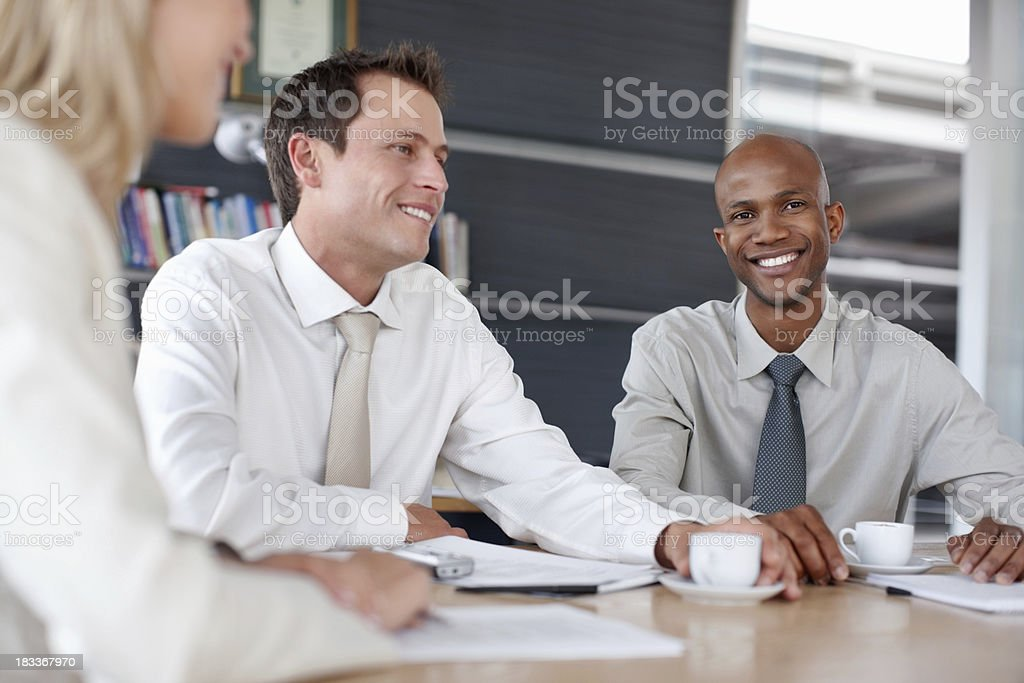 Handsome business man smiling with colleagues at desk royalty-free stock photo