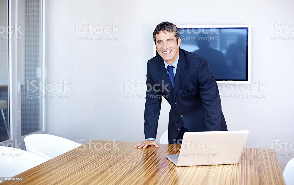 Handsome business man standing with laptop in a boardroom royalty-free stock photo