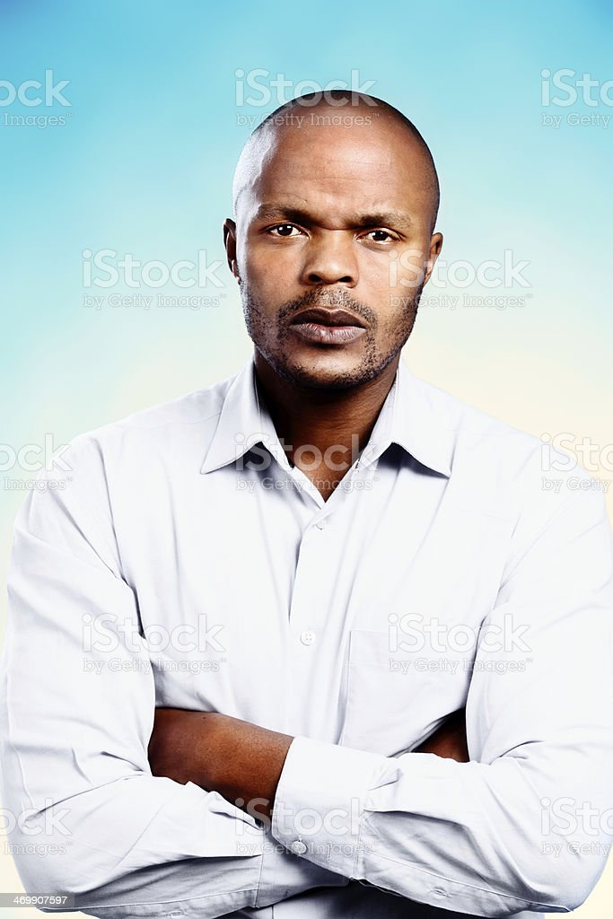 Handsome businessman frowns, arms folded, waiting for your explanation stock photo