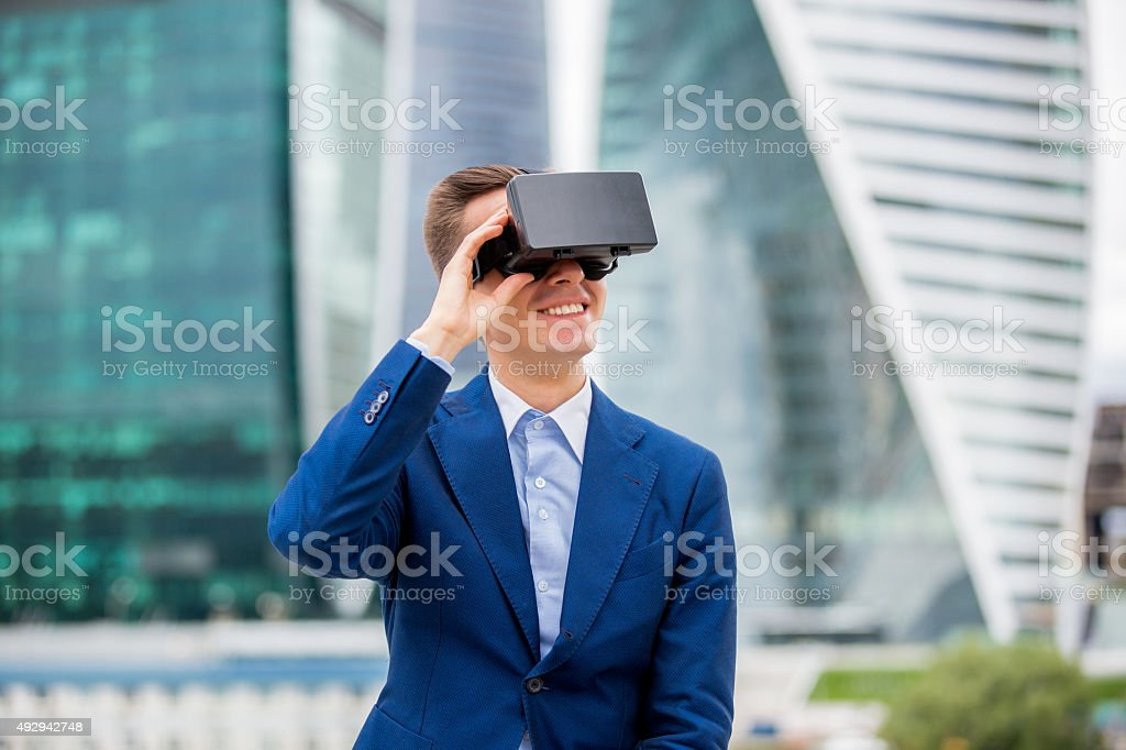 Handsome businessman in suit with head-mounted display on stock photo