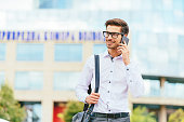 Handsome businessman in white shirt discussing investments on phone