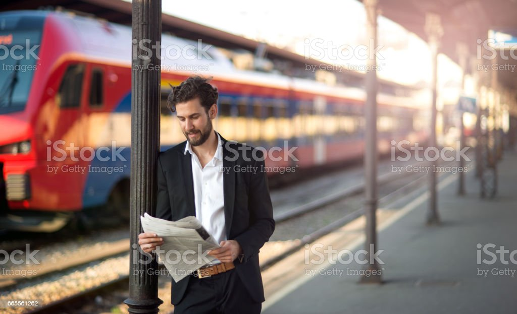 Handsome businessman reading newspapers stock photo