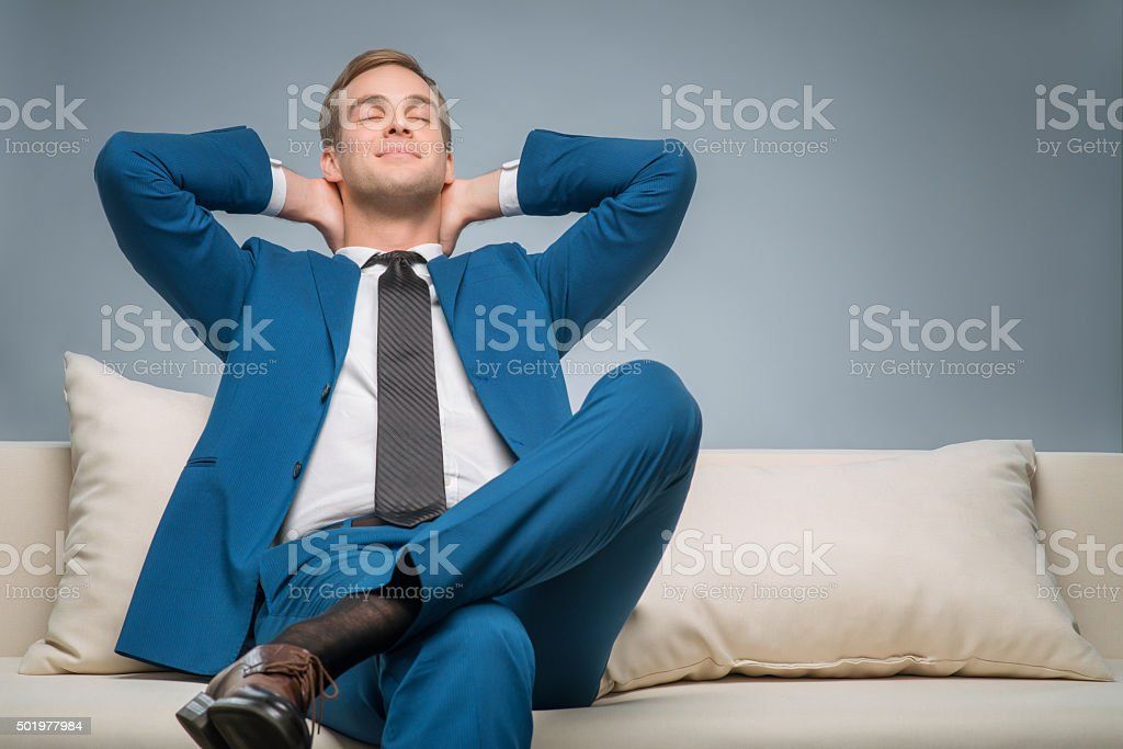 Handsome businessman relaxing on the sofa stock photo