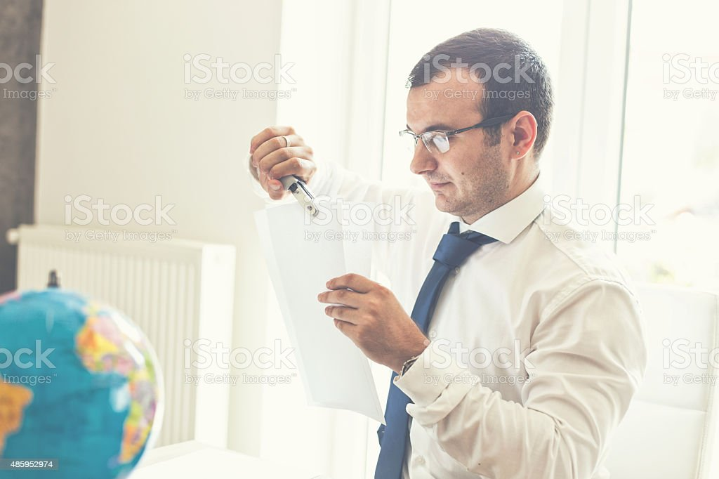 Handsome businessman signing contract in office stock photo