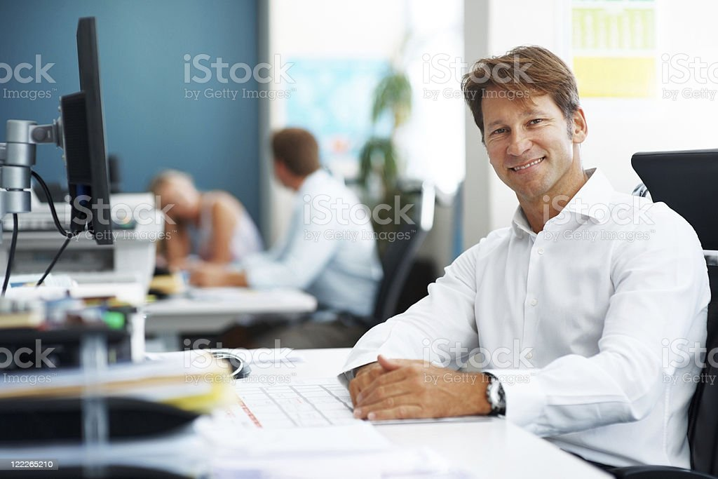 Handsome businessman sitting at his desk royalty-free stock photo