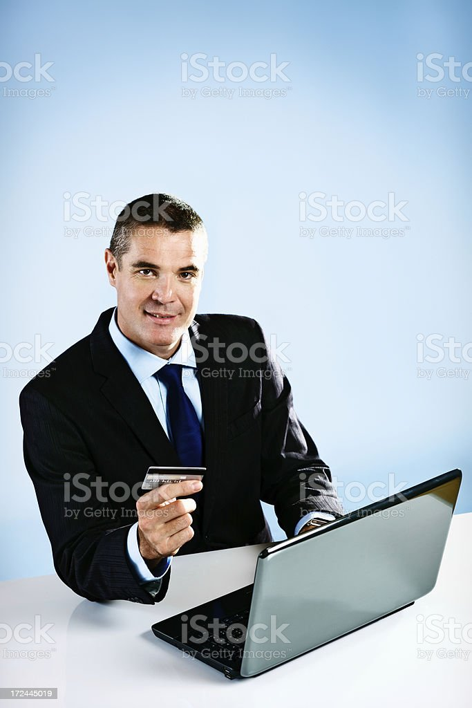 Handsome businessman smiles as he does some e-commerce royalty-free stock photo