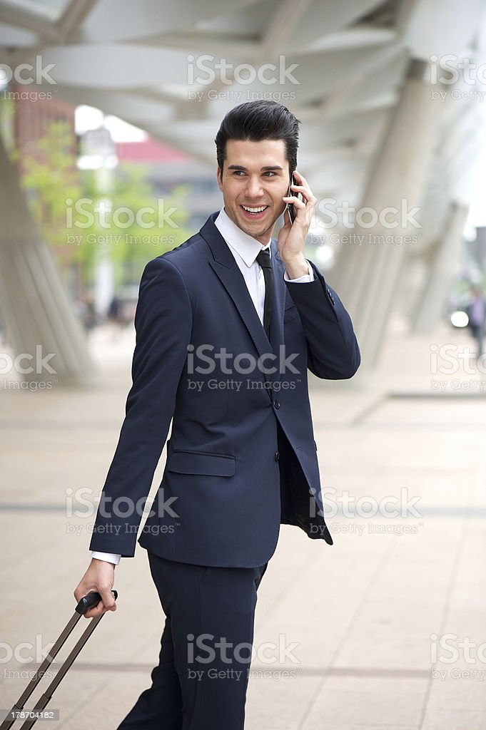 Handsome businessman talking on phone and walking outdoors royalty-free stock photo