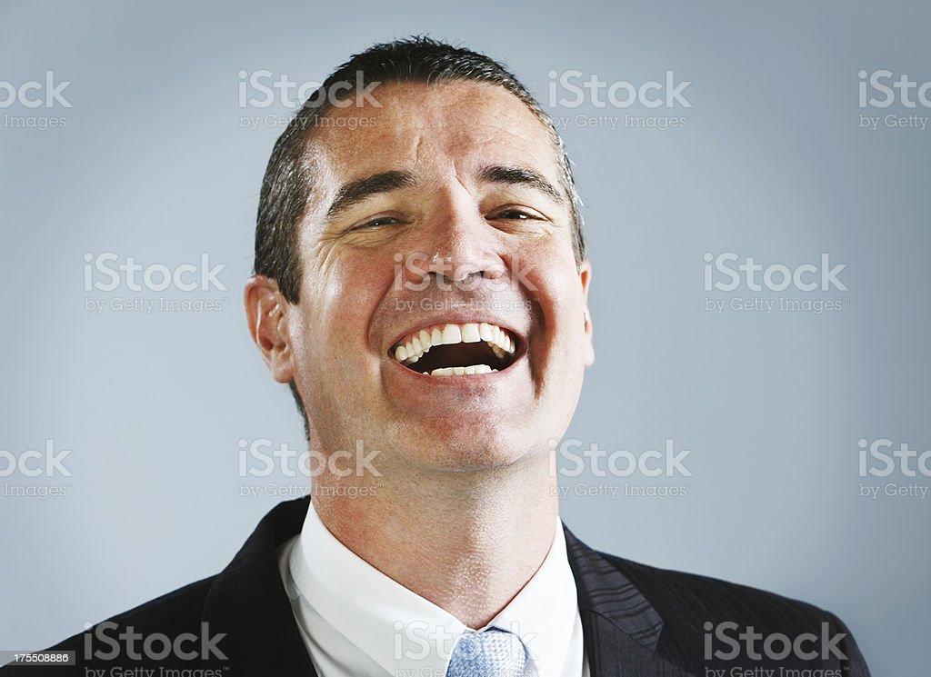 Handsome businessman tilts head back as he laughs stock photo