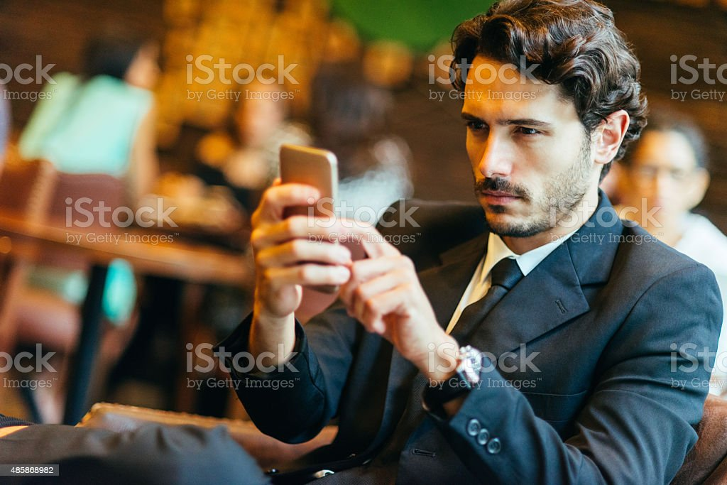 handsome businessman typing text message while relaxing in the bar stock photo