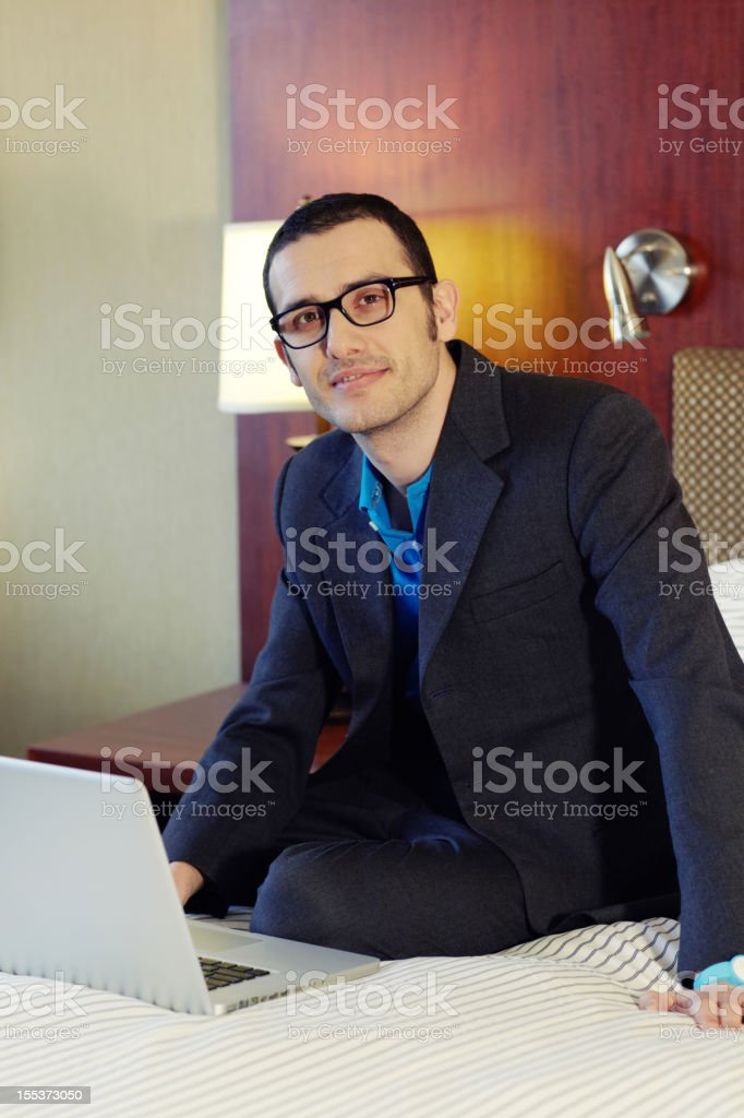 Handsome businessman working on laptop in hotel room stock photo