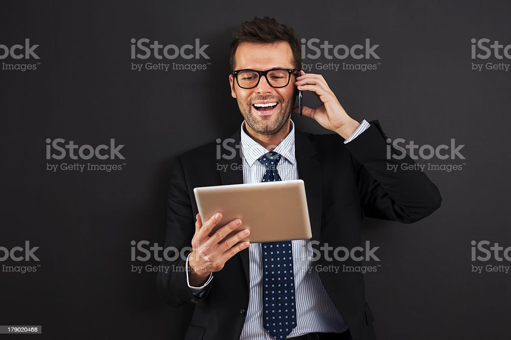 Handsome businessman working with mobile phone and digital tablet royalty-free stock photo