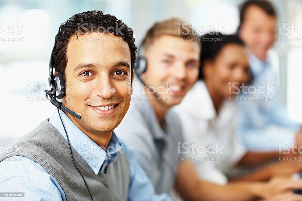 Handsome call centre employee with colleagues at the back royalty-free stock photo