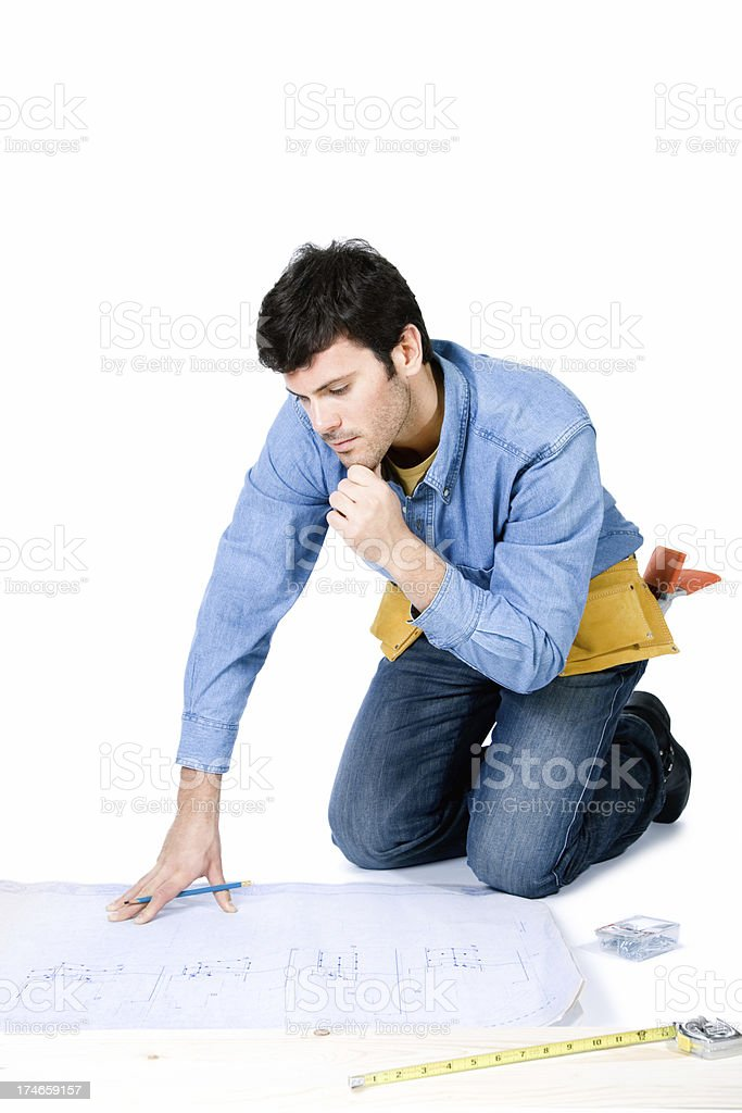 handsome carpenter sitting on the floor looking at architectural plans royalty-free stock photo