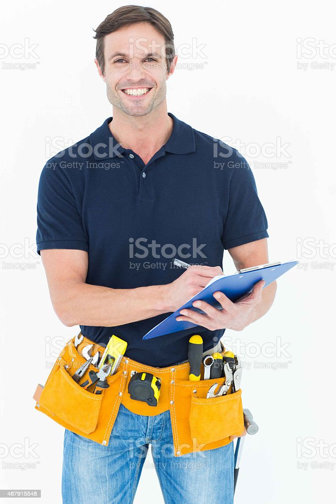 Handsome carpenter writing on clipboard stock photo