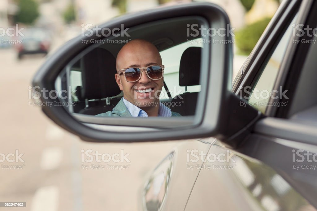 Handsome Caucasian business man looking at you camera through rear view mirror. Horizontal shape, head and shoulders isolated road background stock photo