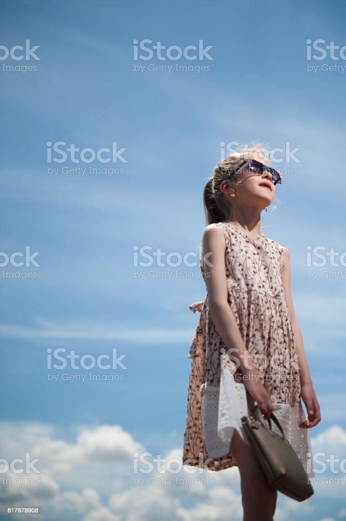 handsome caucasian girl wearing fashionable dress and sunglasses holding handbag on blue sky background stock photo