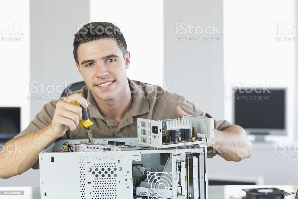 Handsome cheerful computer engineer repairing open Pc stock photo