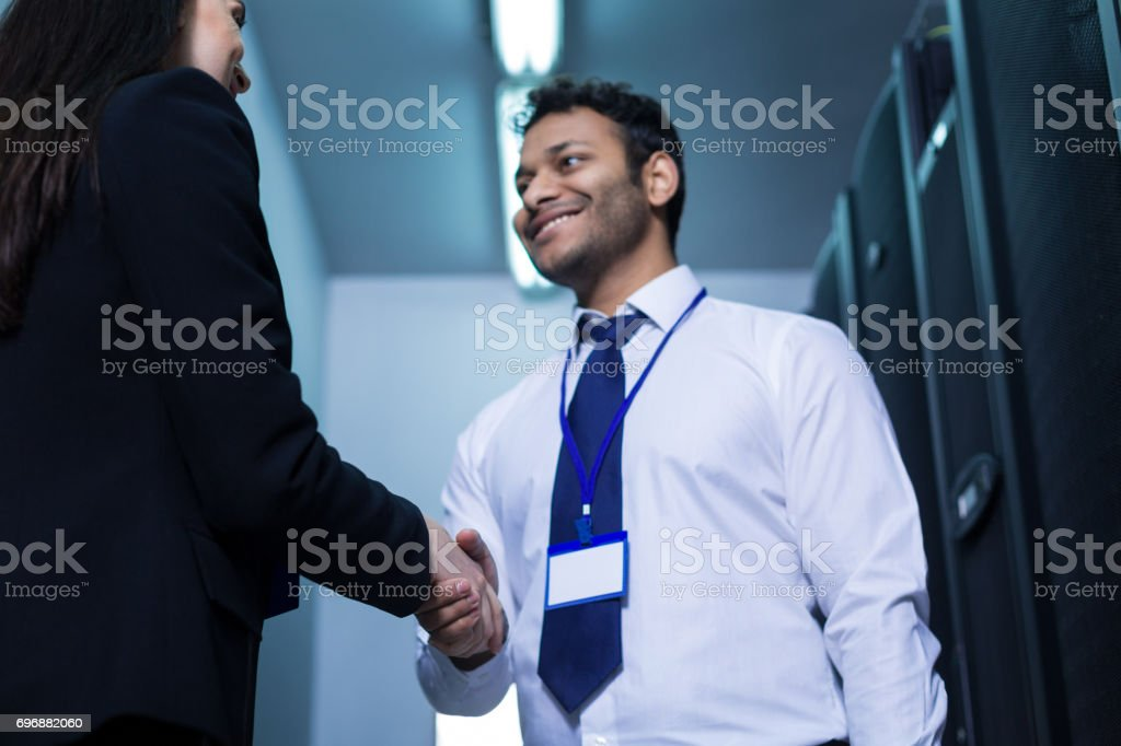 Handsome cheerful man greeting his new colleague stock photo