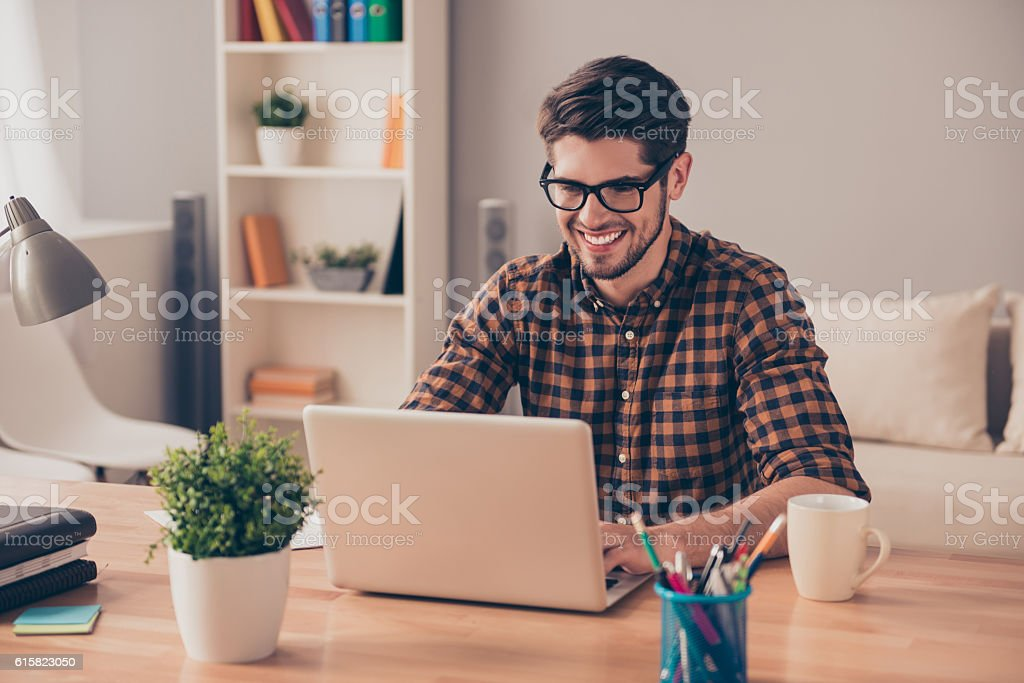 Handsome cheerful young man in glasses typing on laptop stock photo