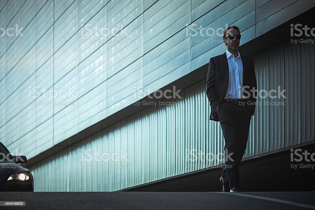 Handsome classy man in suit walks down the city street stock photo